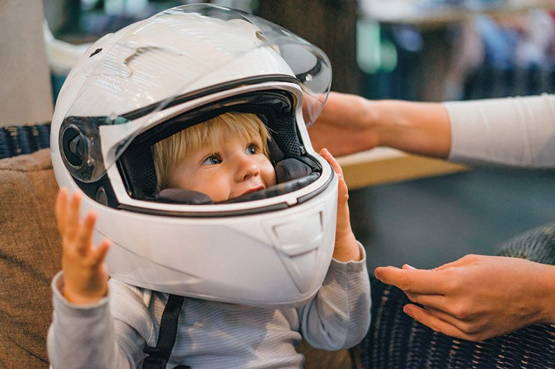 Child wearing adults' motorcycle helmet